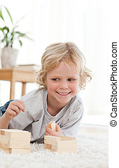 Cute little boy playing with dominoes lying on the floor