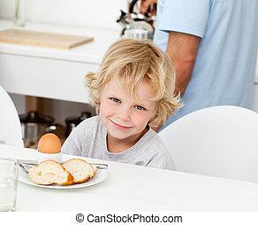 Little boy eating boiled egg