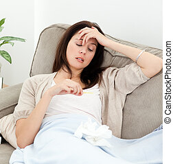 Sick woman looking at a thermometer while resting on the...