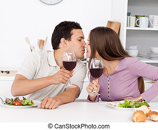 Cute couple giving a toast while having lunch in the kitchen...