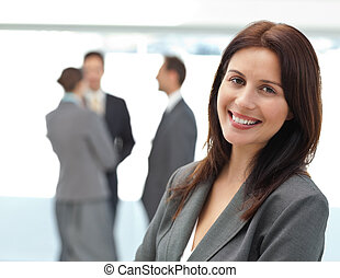 Pretty businesswoman posing in front of her team while...