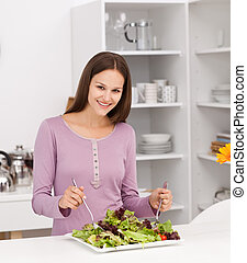 Pretty woman preparing a salad standing in the kitchen at...