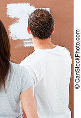 Rear view of a man painting a wall in white with his...
