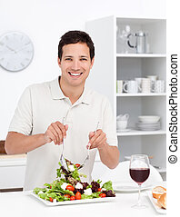 Happy man mixing a salad standing in the kitchen at home