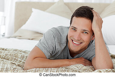 Joyful man lying on th edge of his bed at home and looking...