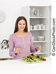 Cute woman mixing a salad standing in the kitchen at home