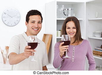 Young couple toasting with glasses of red wine - Young...