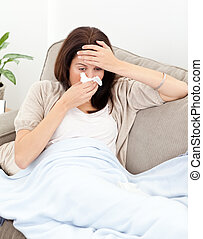 Tired woman feeling her temperature while blowing her nose...