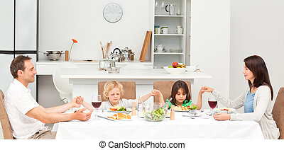 Concentrated family praying before having lunch in the...