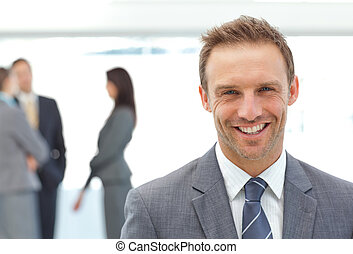 Happy businessman posing in front of his team while working...