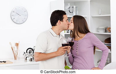 Cute couple kissing with glasses of red wine in their hands...