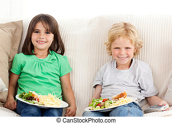 Happy brother and sister having TV dinner