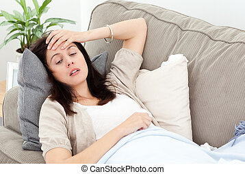 Indisposed woman feeling her temperature while resting on...