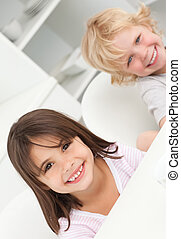 Cute brother and sister sitting at a table in the kitchen