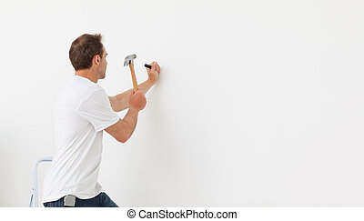 Rear view of a man hammering against a white wall standing...