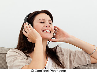 Happy woman enjoying a song on the sofa at home