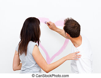 Rear view of a man drawing a heart for his girlfriend while...