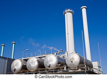 Tanks and smokestacks in front of a blue sky