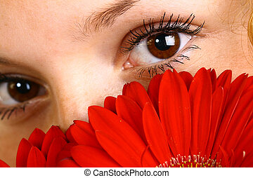 eyes - The fine girl looks eyes because of a red flower at...