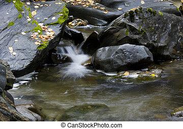 trickle of water between jet black boulders