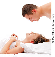 Man bending over woman - Young couple in bed, man bending...