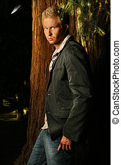 Male model standing by a tree at night