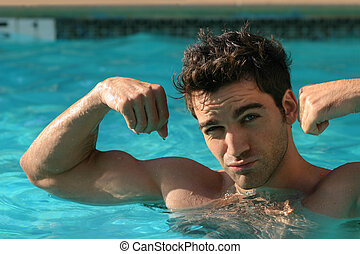 Flexing - Young man flexing his muscles in pool making a...