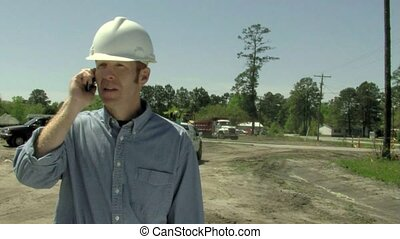 Man in hard hat talks on phone at a construction site....