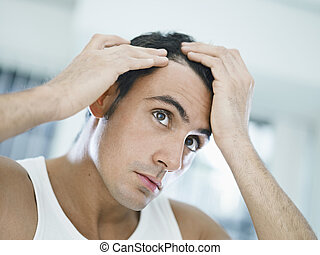 male beauty - caucasian adult man checking hairline...