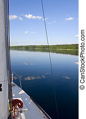 Sailboat on a beautiful lake, clouds reflected in water