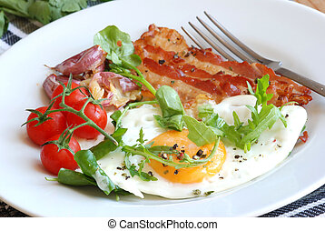 English breakfast - Fried egg, bacon, tomatoes and rocket on...