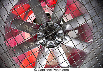 Industrial fan behind a metal grate,