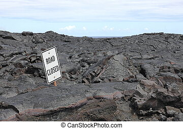 Road closed sign in the middle of lava field on Big Island,...
