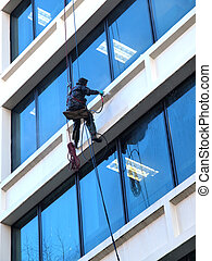 Pressure washing a building. - A man hanging by the ropes...