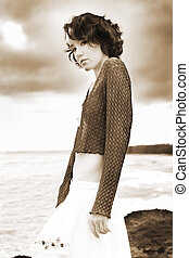 Sepia portrait - A beautiful girl stands on a headland...