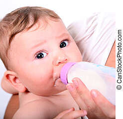 A baby eating milk from the bottle isolated on white