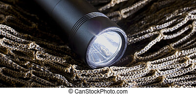Flashlight - Black tactical flashlight that is on brown...