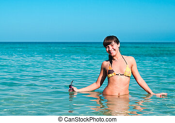 Young pretty girl laying on a sandy beach near the shore blue sea