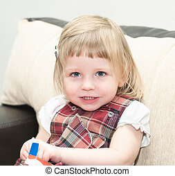 Portriat of little girl in domestic life. Blond hair. Looking at camera