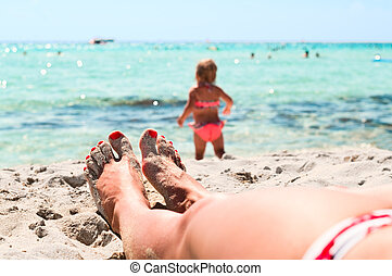 Legs of beautiful young unrecognizable girl lying on sand in beach near a sea and little playing child