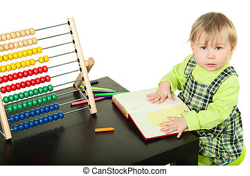 The little girl sits at a table and does a homework, draws in a notebook. Isolated on a white background
