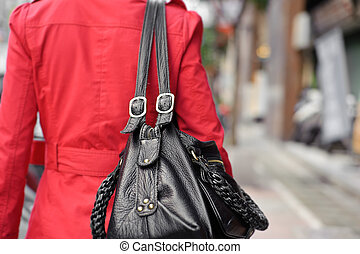 Single woman holding bag and walking in street, closeup...