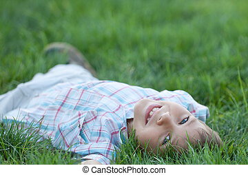 Kid lying in the green grass - A smiling boy is lying in the...