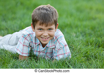 Smiling kid on the green grass - A smiling boy is lying in...