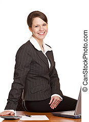 Attractive happy business woman sitting in office at desk