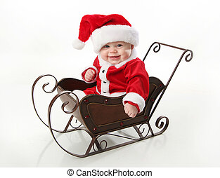 Smiling santa baby sitting in a sleigh - Adorable young baby...