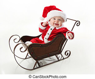 Smilng santa baby sitting in a sleigh - Adorable young baby...