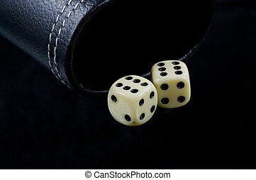 Two dice on black - Two standard six-sided pipped dice with...