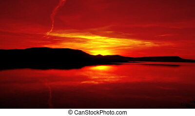 red sunrise on morning lake with mountain