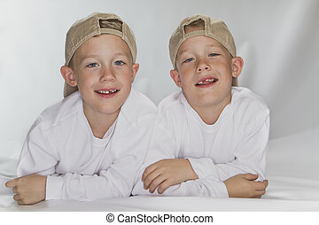 6 years pld identical twins laying on the floor smiling...